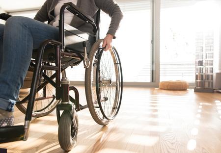 Onherkenbaar gehandicapte senior vrouw in rolstoel thuis.
