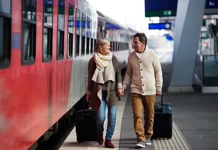 トロリー荷物を引っ張って駅上のシニアのカップル。 写真素材