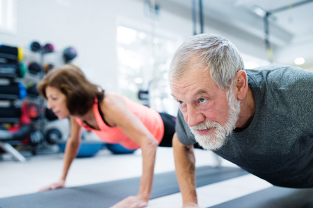 Senior paar in de sportschool uit te werken, doet push ups Stockfoto