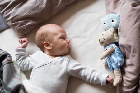 plushie: Cute newborn baby boy with teddy bear lying on bed