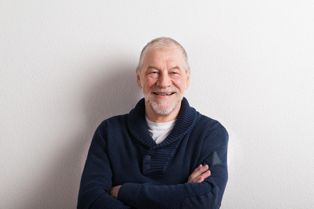 one man: Senior man in blue woolen sweater, studio shot.