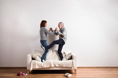 Schöne Senior Paar auf der Couch stehen, tanzen. Studio gedreht. Standard-Bild - 73234810