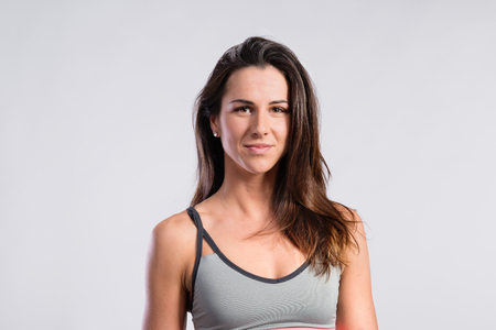 Attractive young fitness woman in gray tank top. Studio shot. Stock Photo