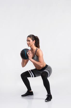 Fitness Frau in Sportbekleidung halten Medizin Ball, Studio s