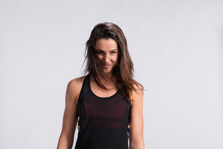 Fitness woman in black tank top, flipping her hair. Studio shot.