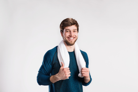Handsome fitness man resting after working out, towel around nec Stock Photo