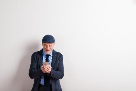 Senior man in jas, bril en pet, met smartphone