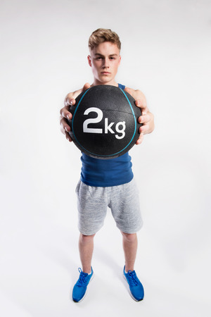 Handsome fitness man holding medicine ball, studio shot. Stock Photo