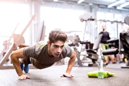 Junge fit hispanischen Mann in der Turnhalle tun Push-ups Standard-Bild - 74320889