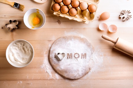 Mothers day composition. Baking ingredients and kitchen utensils laid on table. I love Mom sign made of flour and cookie cutter. Studio shot on wooden background.