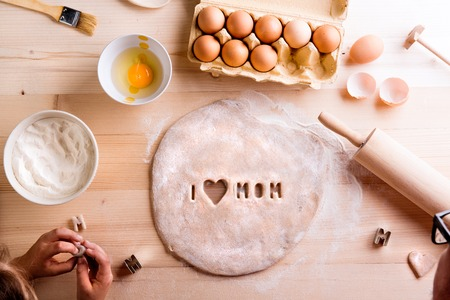 Mothers day composition. Hands of unrecognizable girl baking cookies, playing with dough. I love Mom sign made with cookie cutter. Studio shot on wooden background.