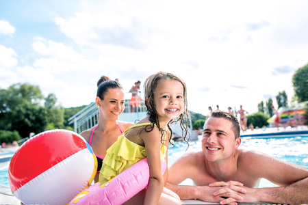 ball on water: Mother, father and daughter in swimming pool. Sunny summer.