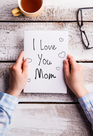 Mothers day composition. Hands of unrecognizable woman holding note with I love you mom text. Cup of tea and eyeglasses. Studio shot on white wooden background. Flat lay. Imagens