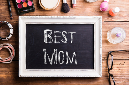 scrunchy: Mothers day composition. White picture frame with black board in it and chalk Best mom sign. Various beauty products laid on table. Studio shot on wooden background. Flat lay.