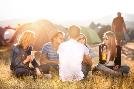 Teenagers sitting on the ground in front of tents, eating Stock Photo