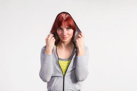 Attractive young fitness woman in gray sweatshirt. Studio shot.