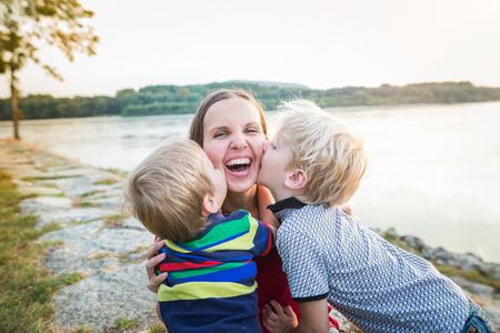upbringing: Mother with two sons at the lake, sunny spring day.