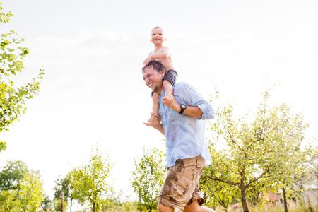 Kleiner Junge mit seinem Vater beim Sprinkler, Sommer