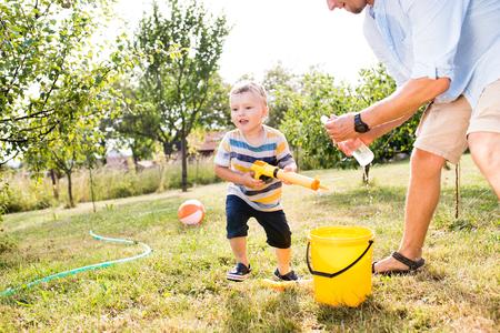 Kleine jongen met vader die met waterpistolen speelt, spatten