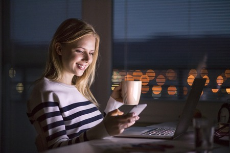Woman at desk, holding smartphone, working on laptop at night.
