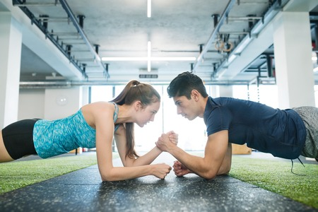 Young fit couple in gym in plank position exercising core muscle