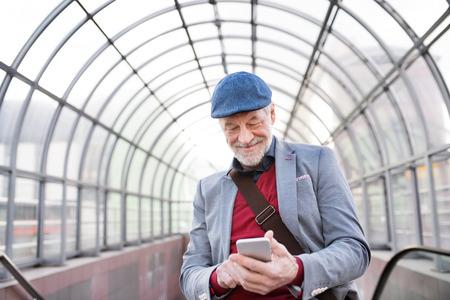 ガラス天井のテキスト メッセージに対してスマート フォンで年配の男性。