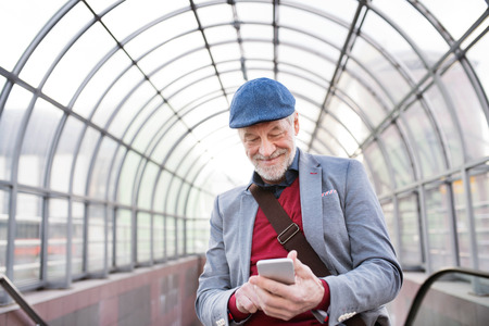 Senior man with smartphone against glass ceiling texting.