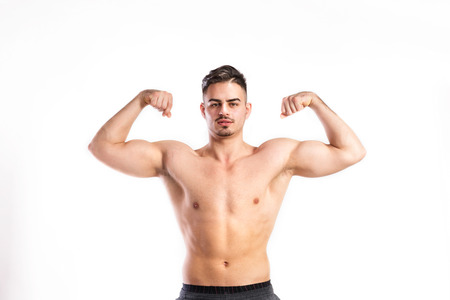 tummy time: Shirtless fitness man flexing his arms. Studio shot. Stock Photo