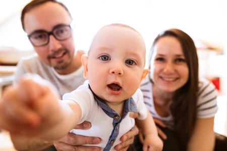 Mooie jonge ouders houden hun schattige baby zoon Stockfoto