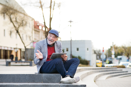 sitting on the ground: Handsome senior man with tablet in town sitting on stairs.