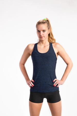 Attractive young fitness woman in blue tank top. Studio shot. Stock Photo