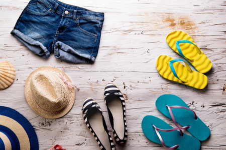 Summer vacation composition. Denim shorts, hats and flip flops. Stock Photo