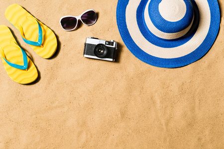 Pair of flip flop sandals, sunglasses, hat and camera.