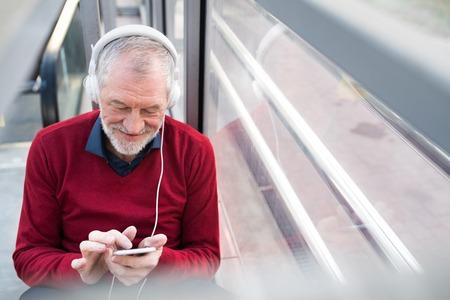 スマート フォンとヘッドフォンの通路に座っている年配の男性。 写真素材