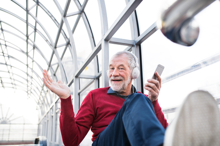 Senior man with smartphone and headphones sitting in passage. Stock Photo
