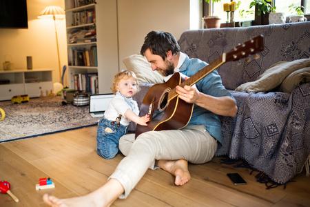 Padre e hijo en casa tocando la guitarra juntos. Foto de archivo - 78800827
