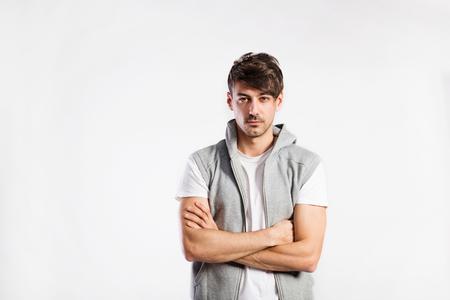 hooded vest: Handsome fitness man in vest with hood, studio shot.