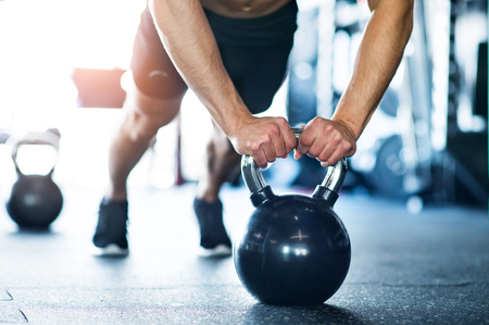 Onherkenbaar fit man in de sportschool doet push ups op kettlebells Stockfoto