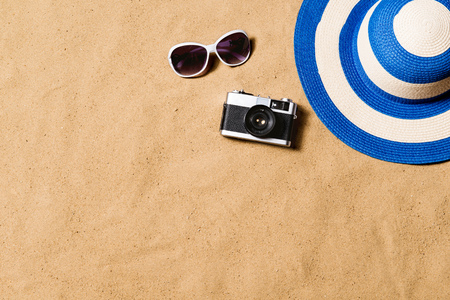 Sunglasses, wicker hat and camera. Sand background.