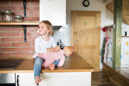 Little girl with doll sitting on kitchen countertop