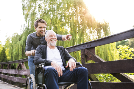 Hipster son walking with disabled father in wheelchair at park. Stok Fotoğraf - 79756383