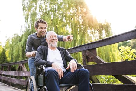 Hipster zoon wandelen met gehandicapte vader in rolstoel op park.