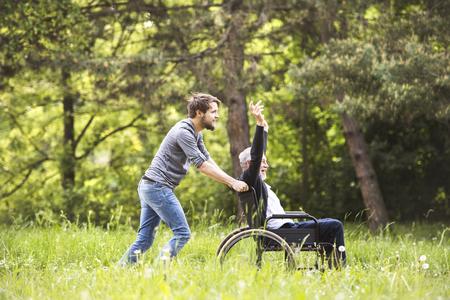 流行に敏感な息子とウォーキングには、公園で車椅子の父が無効になります。