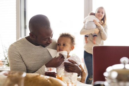 Young interracial family with little children having breakfast. Stock Photo