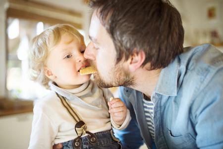 ビスケットを一緒に食べて少し息子と若い父の自宅で。 写真素材