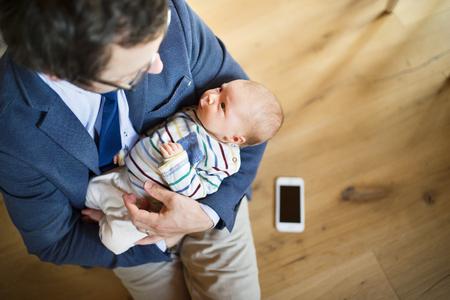 Zakenman thuis met een baby dochter in de armen.