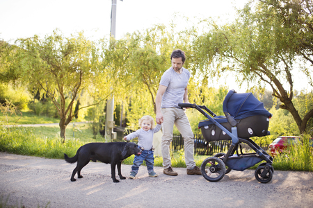 Father with son and baby daughter in stroller. Sunny park. Stock Photo