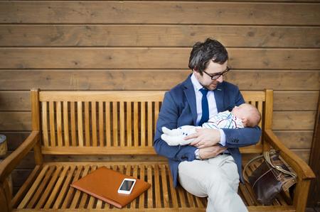 Zakenman met baby dochter zitten op de voorportaal. Stockfoto