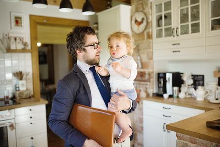 Zakenman naar huis, met kleine zoon in de armen.