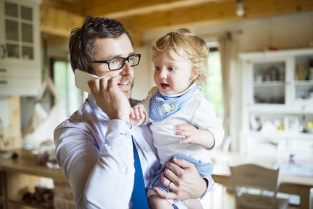 Businessman with smartphone at home with son in the arms. Stock Photo